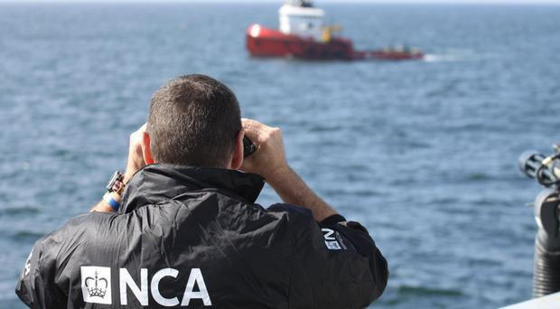 The MV Hamal tug being watched by an NCA officer as it was intercepted by the frigate HMS Somerset and Border Force cutter Valiant (PA/National Crime Agency)