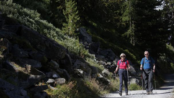 Prime Minister Theresa May and her husband Philip hike through a Swiss forest on the first day of their summer holiday