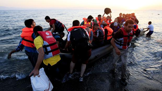Migrants and refugees arrive in a rubber dinghy
