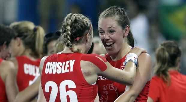 Britain's Giselle Ansley, right, congrats her teammate Lily Owsley, left, after they beat Netherlands in the penalty shootout, during a women's field hockey gold medal match.