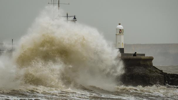 Huge waves crash against the harbour wall at Porthcawl, Wales