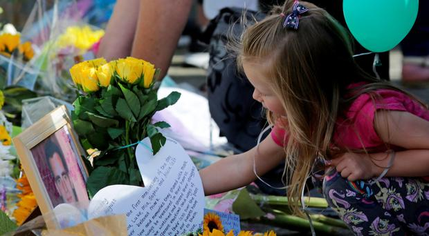 A young girl leaves flowers on the toll bridge in Shoreham, West Sussex, where a memorial service to mark the first anniversary of the Shoreham air crash took place