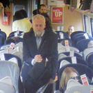 Labour Party leader Jeremy Corbyn walking past unoccupied seats in Coach F (Virgin Trains)