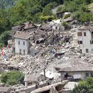 Rescuers search through debris of collapsed houses in Pescara del Tronto (AP)