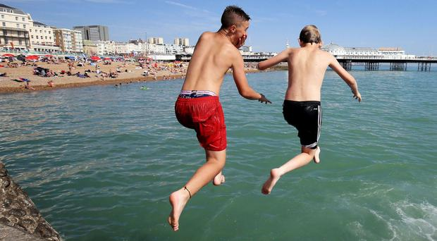 Boys jump into the sea in Brighton, East Sussex