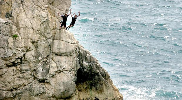 Two men jump off rocks into the sea at Durdle Door near West Lulworth, Dorset