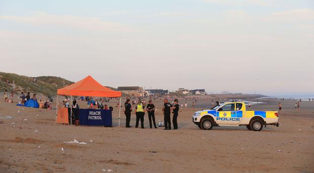 Police officers on Camber Sands after five men died after being pulled from the sea on the hottest day of the year