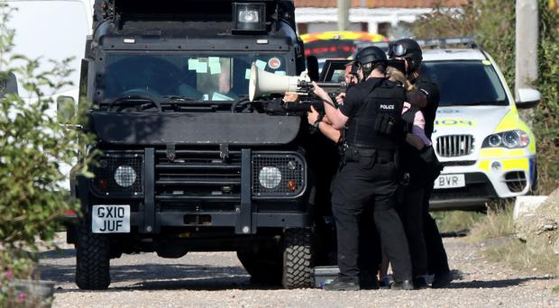 Armed police on Harbour Road, Pagham, West Sussex, where they are in a stand-off with a 72-year-old man who is thought to have a gun