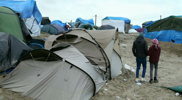 Orphaned refugee children walking amongst the shelters at the Jungle refugee camp at Calais in France