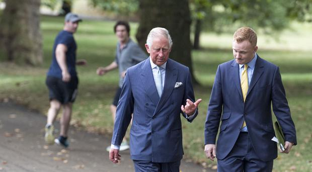 A pair of joggers recognise the Prince of Wales as he walks through Green Park