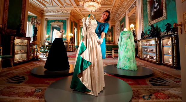 Curator Caroline de Guitaut arranges an evening gown worn by the Queen. Photo: Steve Parsons/PA Wire