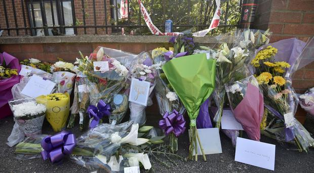 Floral tributes at the scene in Chadwell Heath where a man was fatally stabbed as he confronted a gang of moped thieves