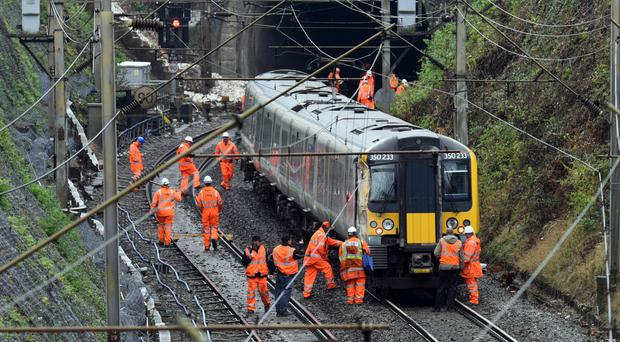 Workers inspect the northbound train which collided into a derailed train near to a landslip near Watford Junction station.