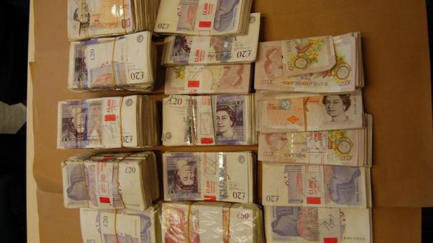 Cash seized by police investigating a multimillion-pound bank fraud and money laundering scam (Met Police/PA)