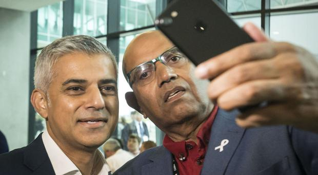 Mayor of London Sadiq Khan (left) stops for a selfie as he arrives for the second day of the Labour Party conference in Liverpool