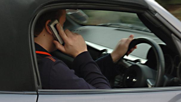 NOTE POSED BY MODEL Undated file photo of a man using his mobile phone while driving as ministers want to double the punishment for illegal mobile phone use, Government sources said.