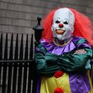 A person wearing a clown costume in a street in Liverpool (posed by a model)
