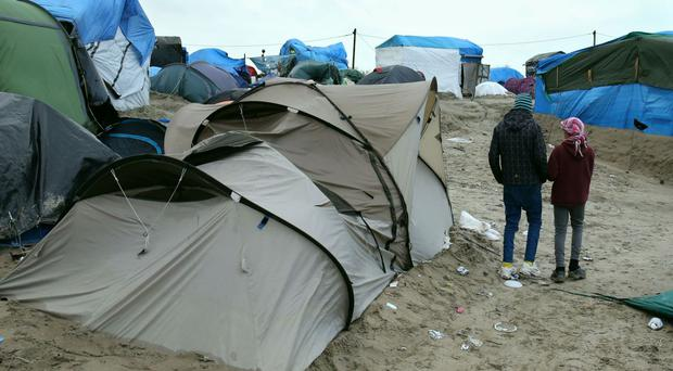 Orphaned refugee children walking among the shelters in the Jungle camp in Calais