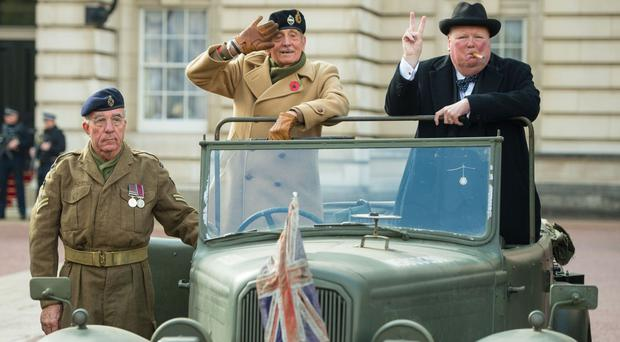 From left to right, Pete Gaine, Mickey Barr and Stan Streather in a 1943 Humber Snipe, part of a display of 90 historic British-built motor vehicles in the forecourt of Buckingham Palace to commemorate the Queen's 90th birthday.