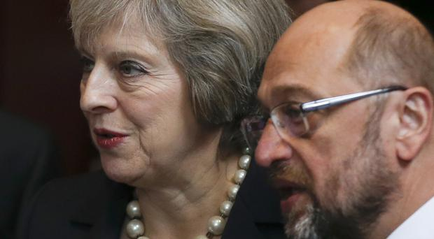 Theresa May talks to European Parliament president Martin Schultz as they arrive for an EU summit group photo (AP)