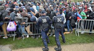 French police push back a large crowd of migrants as they line up at a processing centre in The Jungle