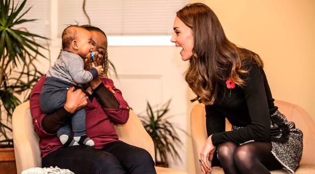 Catherine, Duchess of Cambridge (right), makes faces at four-month-old Gabriel as she talks to his mother Hlengiwe Sithole during a visit to the Nelson Trust Women's Centre in Gloucester