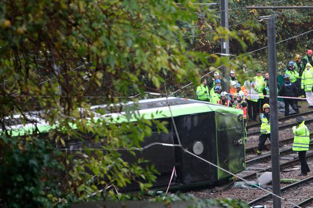The tram lies on its side on the track in Croydon
