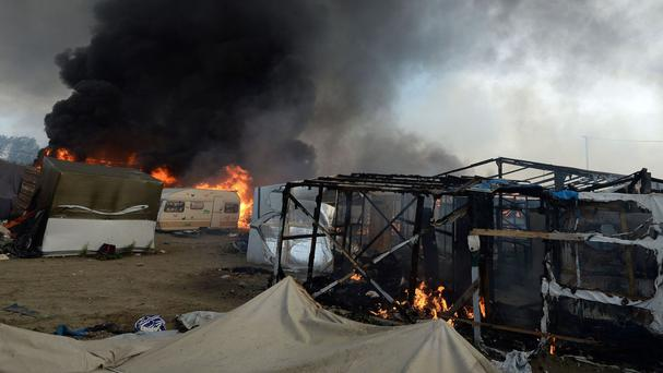 Smoke rises over the Calais Jungle camp during its demolition