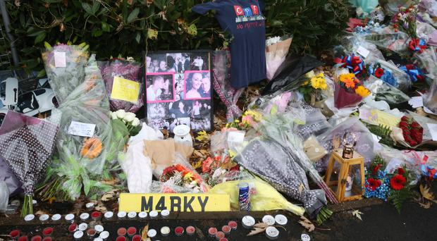 Floral tributes and photographs left near the scene where a tram crashed, killing seven people, in Croydon