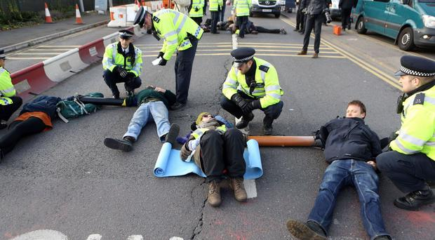 Protesters from campaign group RisingUp! lock themselves together as they block the east ramp at Heathrow Airport in protest over the development of a third runway