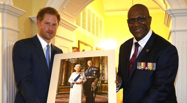 Prince Harry, presents a gift to the His Excellency Sir Rodney Williams during a welcome reception hosted at Clarence House, Antigua