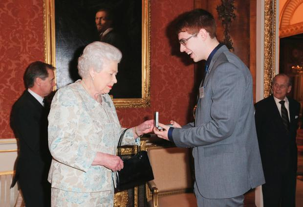 Queen Elizabeth II awards Tyler Bailer a medal during a reception for the Royal Life Saving Society last night