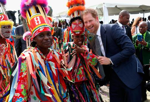 Prince Harry is greeted by cultural dancers at Brimstone Fortress on St Kitts and Nevis during a youth rally on the fourth day of an official visit to the Caribbean