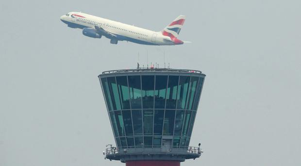 A British Airways plane takes off above the control tower at Heathrow Airport, as the Government was warned over the potential emissions caused by a third runway