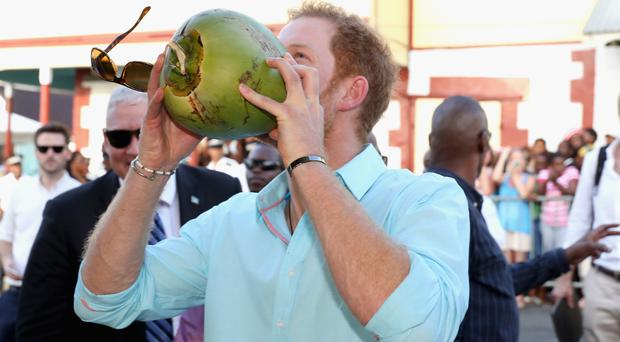 Prince Harry drinks from a coconut while attending a St Lucian street festival in Soufriere