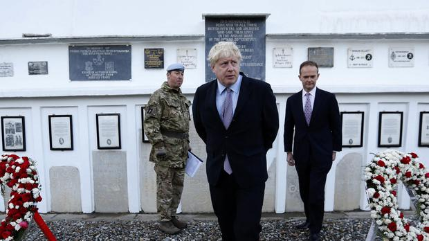 Boris Johnson, centre, and British ambassador to Afghanistan Dominic Jermey, right, visit the British cemetery in Kabul, Afghanistan (Mohammad Ismail, pool via AP)