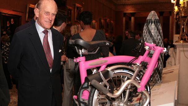The Duke of Edinburgh admires the winner of the Prince Philip Designers' Prize, a pink Brompton fold-up bike, at a reception at Buckingham Palace