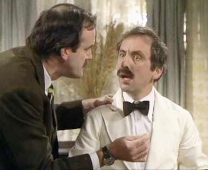 Andrew Sachs (left) and as Manuel alongside John Cleese in Fawlty Towers
