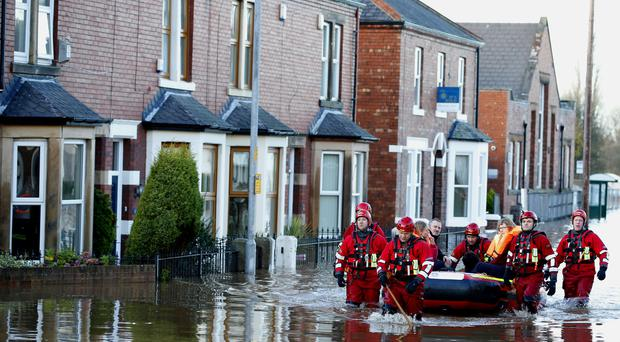 Rescue workers help residents to safety in Carlisle, after heavy rain from Storm Desmond tore through Britain one year ago