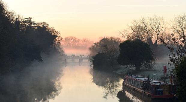 Mist and fog surround a canal boat at Godstow Lock in Oxfordshire