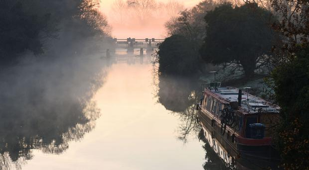 Mist and fog surround a canal boat at Godstow Lock in Oxfordshire.