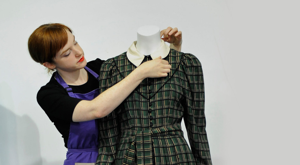 One of the staff at Kerry Taylor Auctions adjusts a dress worn by the Princess of Wales at the Braemar Highland Games in 1982