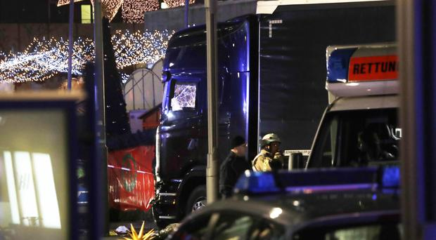 Police stand beside the damaged truck in Berlin (AP)
