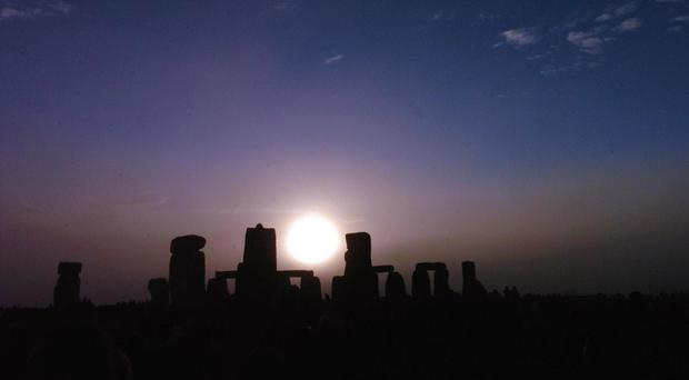 The sun rises over Stonhenge in Wiltshire at dawn.
