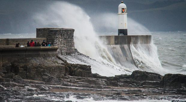 Waves crash over the harbour wall at Porthcawl, as Britain was battered by winds as Storm Barbara swept the country