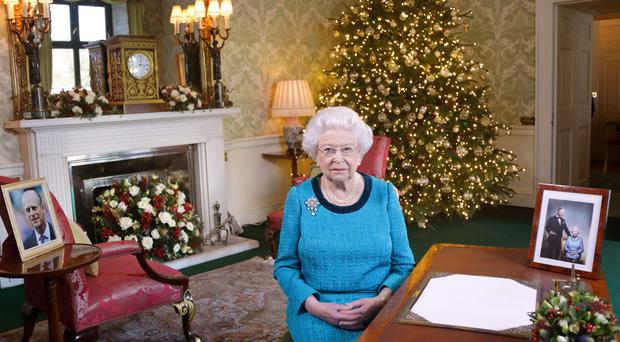 The Queen sits at a desk in the Regency Room in Buckingham Palace, after recording her Christmas Day broadcast to the Commonwealth
