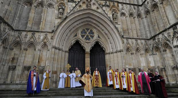 Archbishop of York Dr John Sentamu and minster clergy as they leave York Minster following the Christmas Day Service