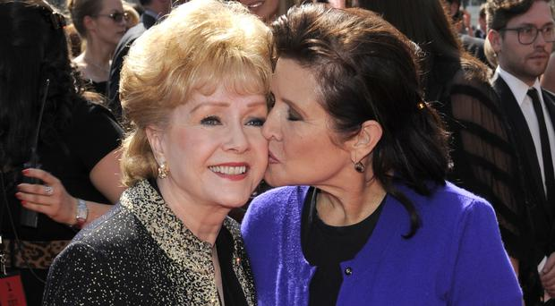 Debbie Reynolds, left, with her daughter Carrie Fisher at the Primetime Creative Arts Emmy Awards in Los Angeles in 2011 (AP)