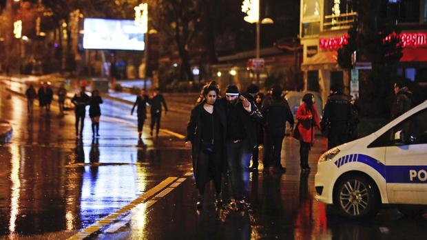 Young people leave the scene of the deadly attack in Istanbul (AP)