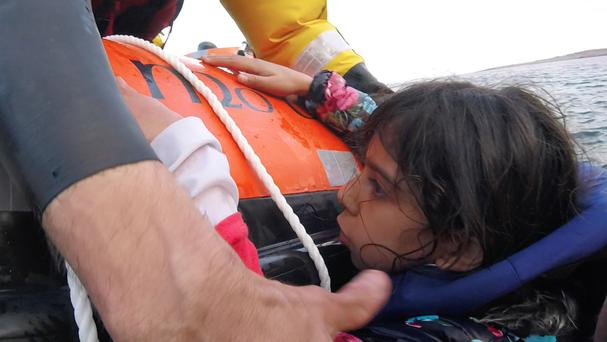 Refugees in the Aegean sea being rescued by a British lifeguard